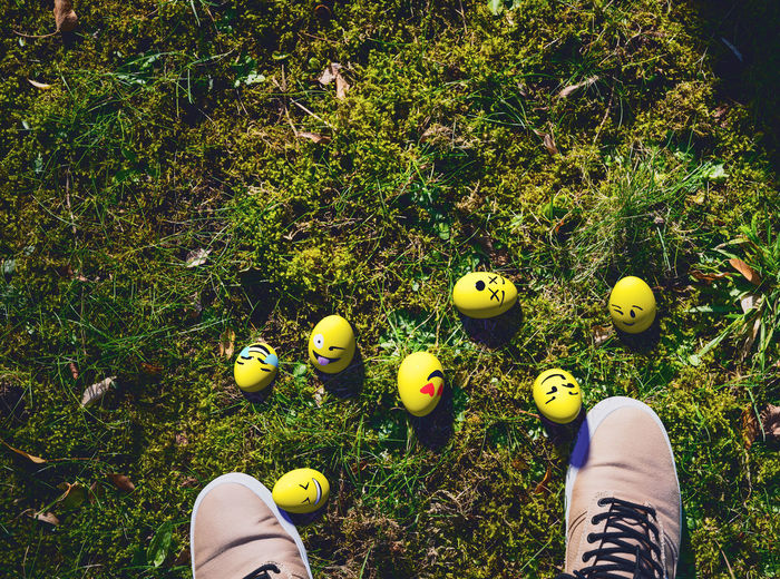 Low Section Of Person With Yellow Easter Eggs Standing On Grassy Field