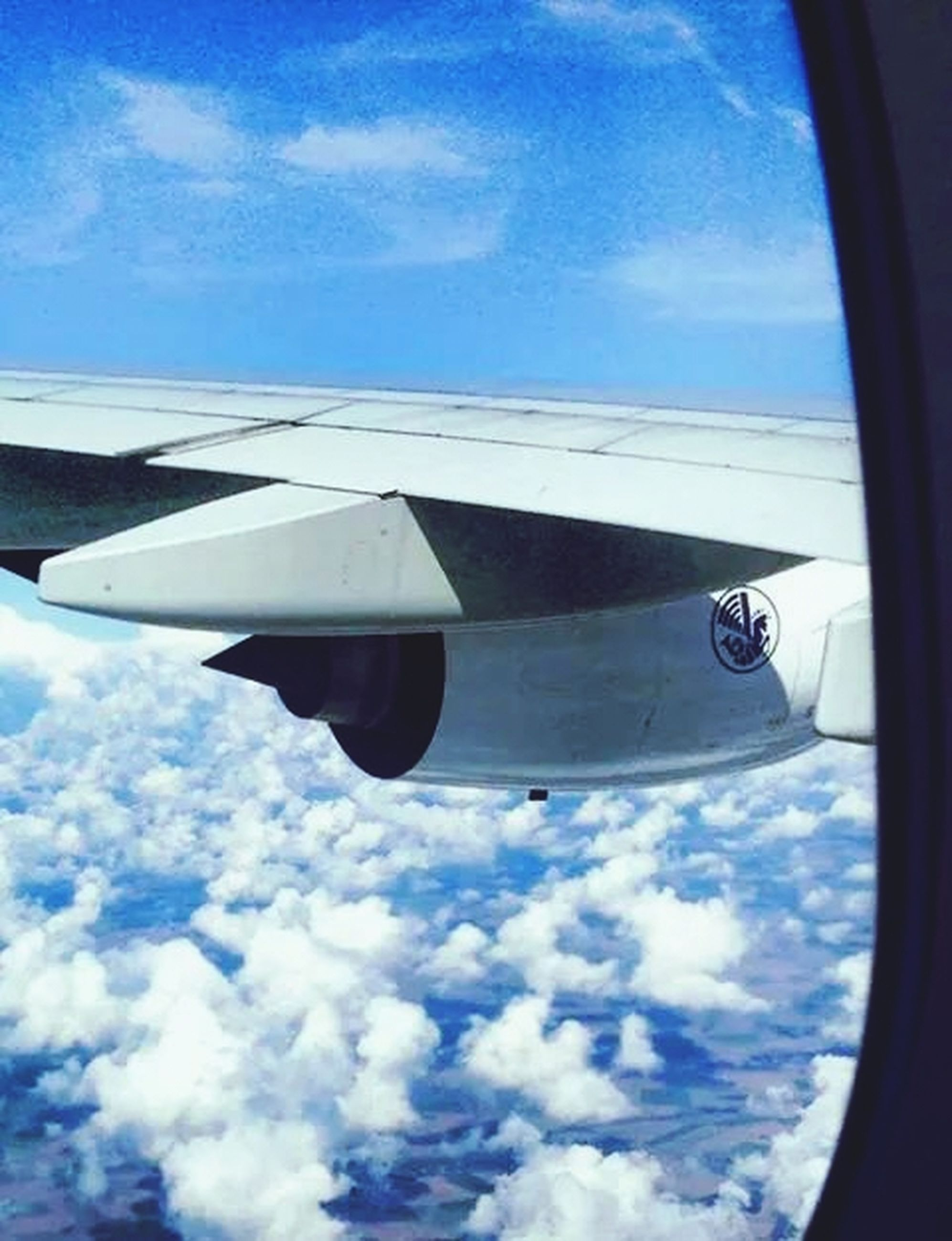 transportation, mode of transport, airplane, air vehicle, sky, cloud - sky, part of, travel, flying, vehicle interior, aircraft wing, public transportation, cropped, journey, window, vehicle part, glass - material, cloud, blue, mid-air