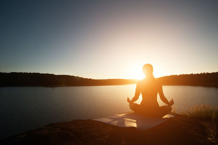 Rear view of woman meditating while sitting on rock at lakeshore during sunset