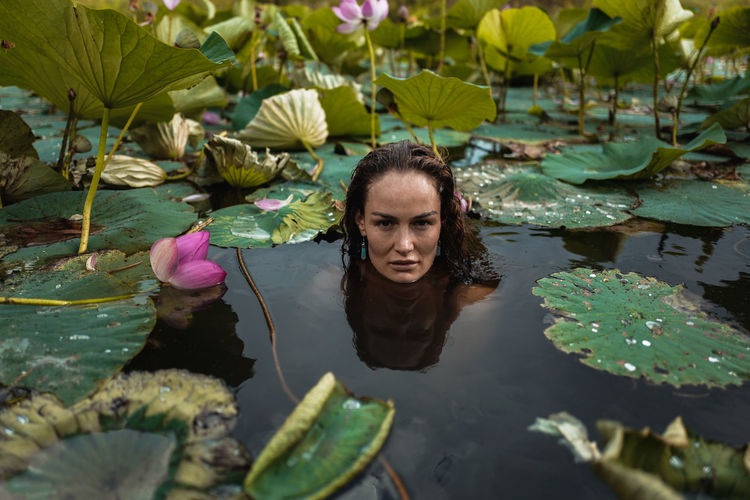 Portrait of woman with leaves in lake
