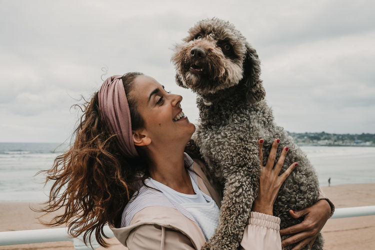 Smiling woman carrying dog while standing at beach