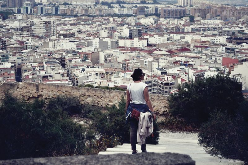 Rear View Of Woman Looking At Buildings In City
