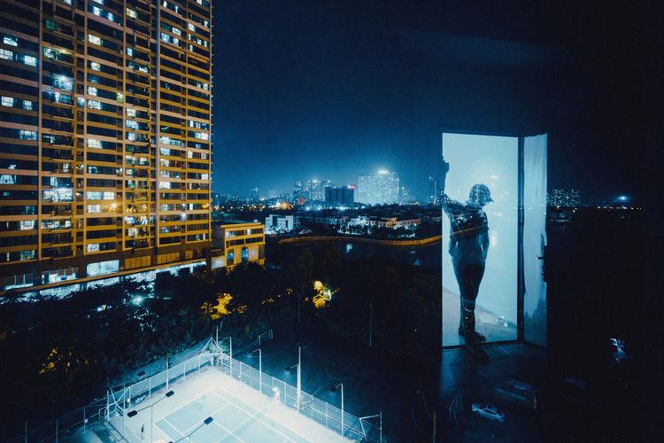 Digital composite image of illuminated modern buildings at night