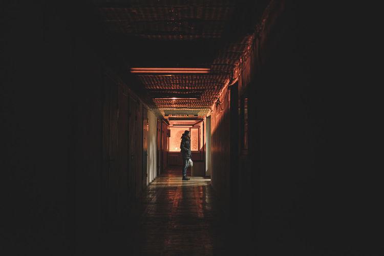 Side view of man standing in building corridor