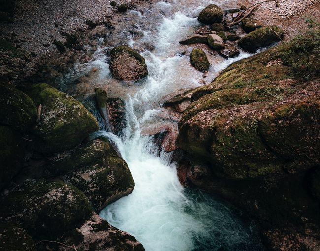 High Angle View Of Stream Flowing Amidst Rocks