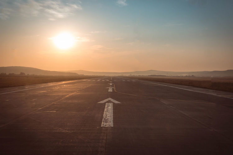 Airport runway against sky during sunset