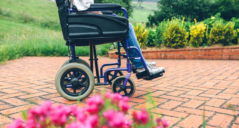 Low Section Of Woman Sitting On Wheelchair At Park