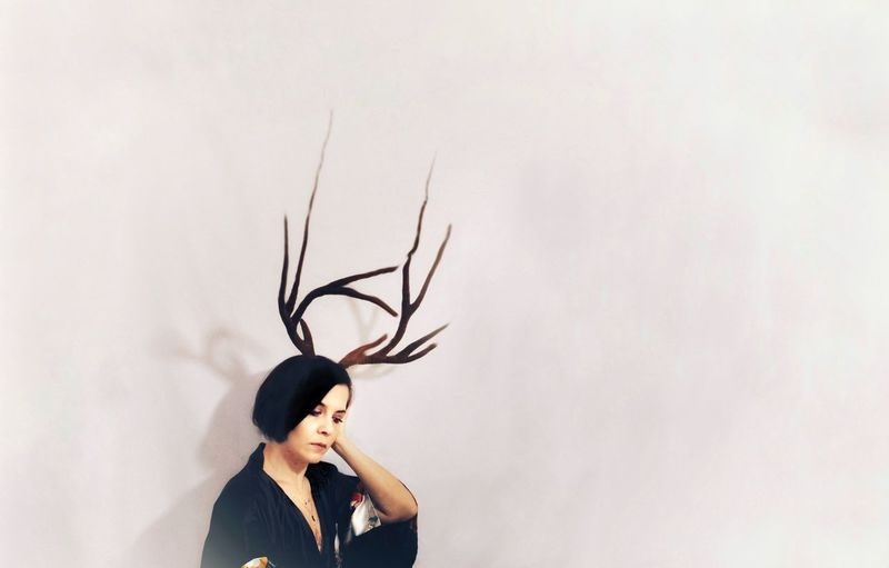 Contemplating woman with artificial antler standing against wall