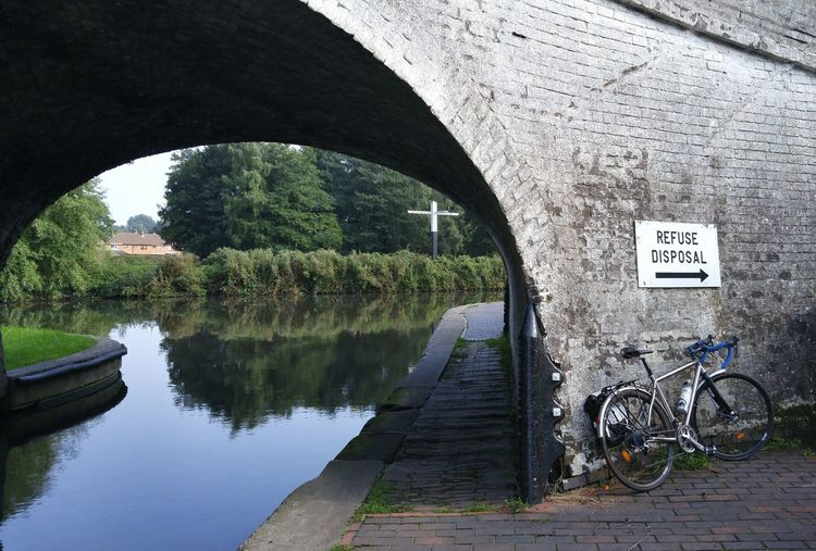 Bicycle parked by information sign on bridge over canal