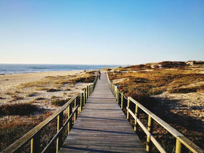 Boardwalk at beach against clear sky