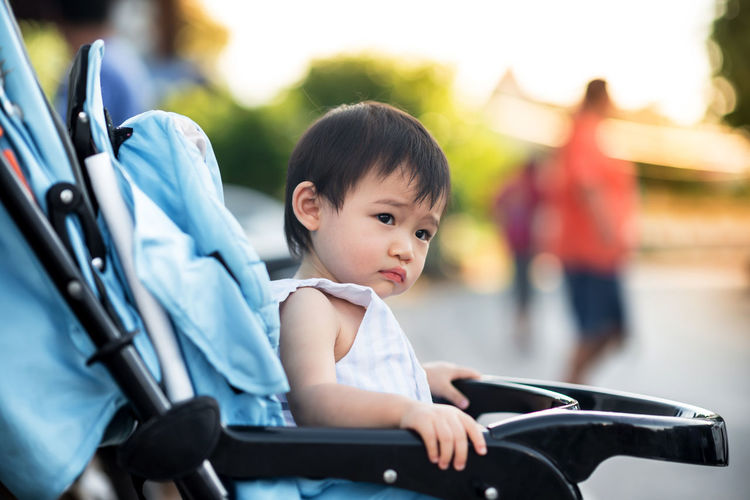 Baby Looking Away While Sitting In Carriage Outdoors