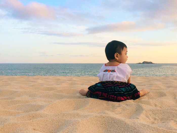 Boy sitting on beach against sky during sunset