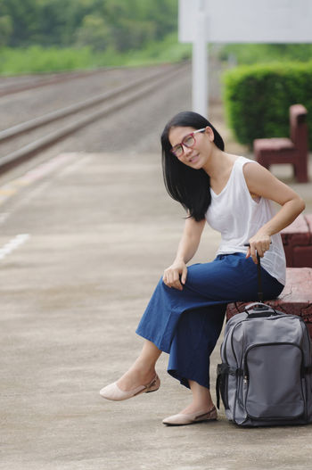 Portrait Of Woman With Backpack Sitting On Railroad Station Platform