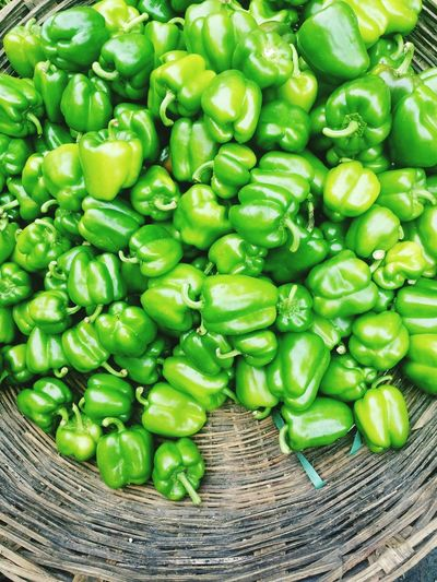 High Angle View Of Green Bell Peppers In Wicker Basket For Sale