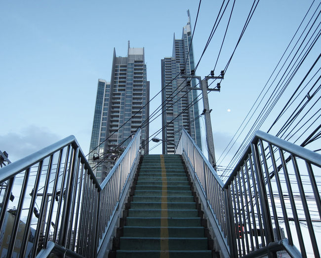 Low angle view of steps and modern buildings against sky in city