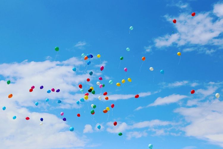 Low Angle View Of Helium Balloons Flying Against Blue Sky