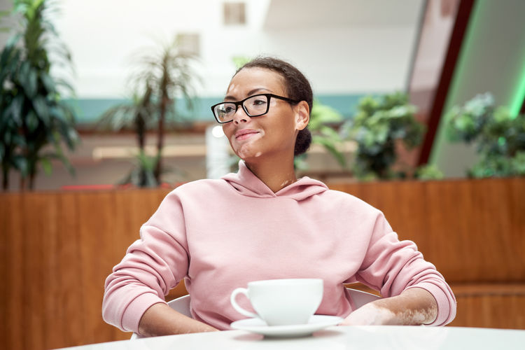 Portrait of smiling woman with coffee cup on table