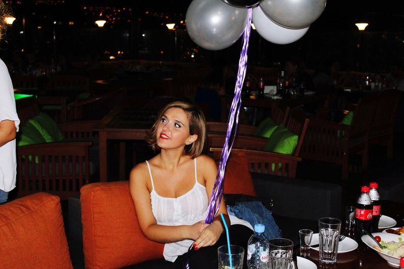 Beautiful woman holding helium balloons while sitting at restaurant