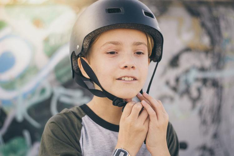 Close-up of boy wearing crash helmet outdoors