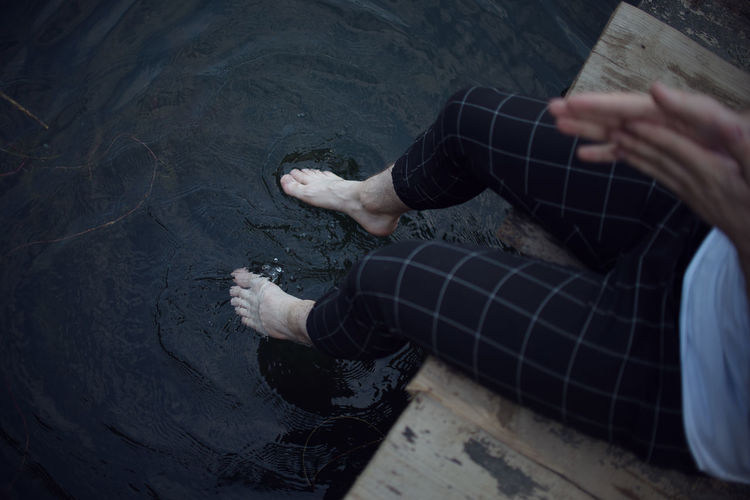 Low section of man relaxing on water