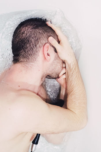 High Angle View Of Shirtless Man Lying In Bathtub