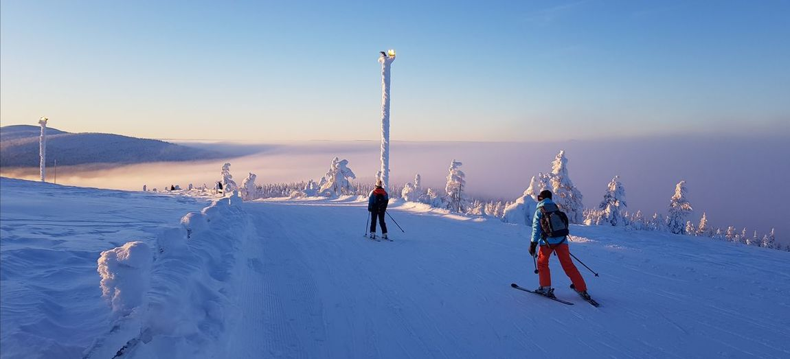 Friends skiing on snow covered landscape during winter