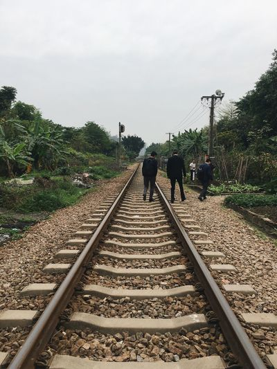 People walking on railroad track against sky
