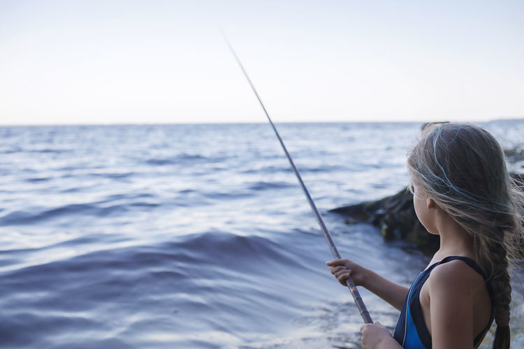 Woman holding fishing rod by sea against sky