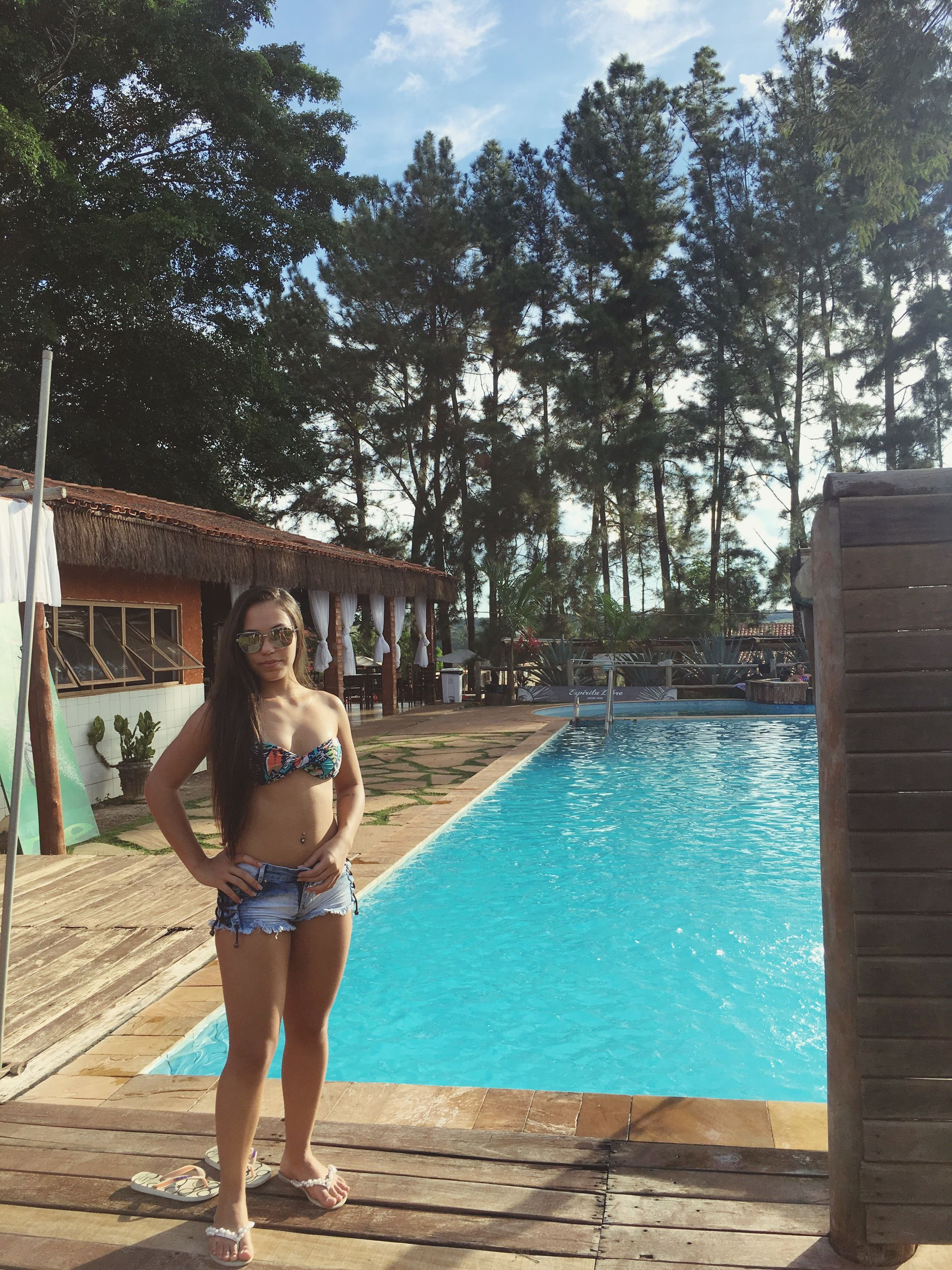 tree, full length, one person, real people, leisure activity, outdoors, day, water, swimming pool, standing, front view, lifestyles, young women, young adult, sky, nature