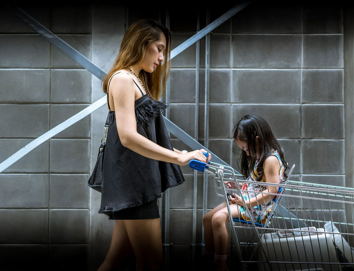 Mom Places daughter In Shopping Cart Young Adult Young Women Women Real People Standing Holding Lifestyles Hair Two People Three Quarter Length Indoors  Adult People Casual Clothing Hairstyle Long Hair Brown Hair Wall - Building Feature Beautiful Woman Fashion Consumerism