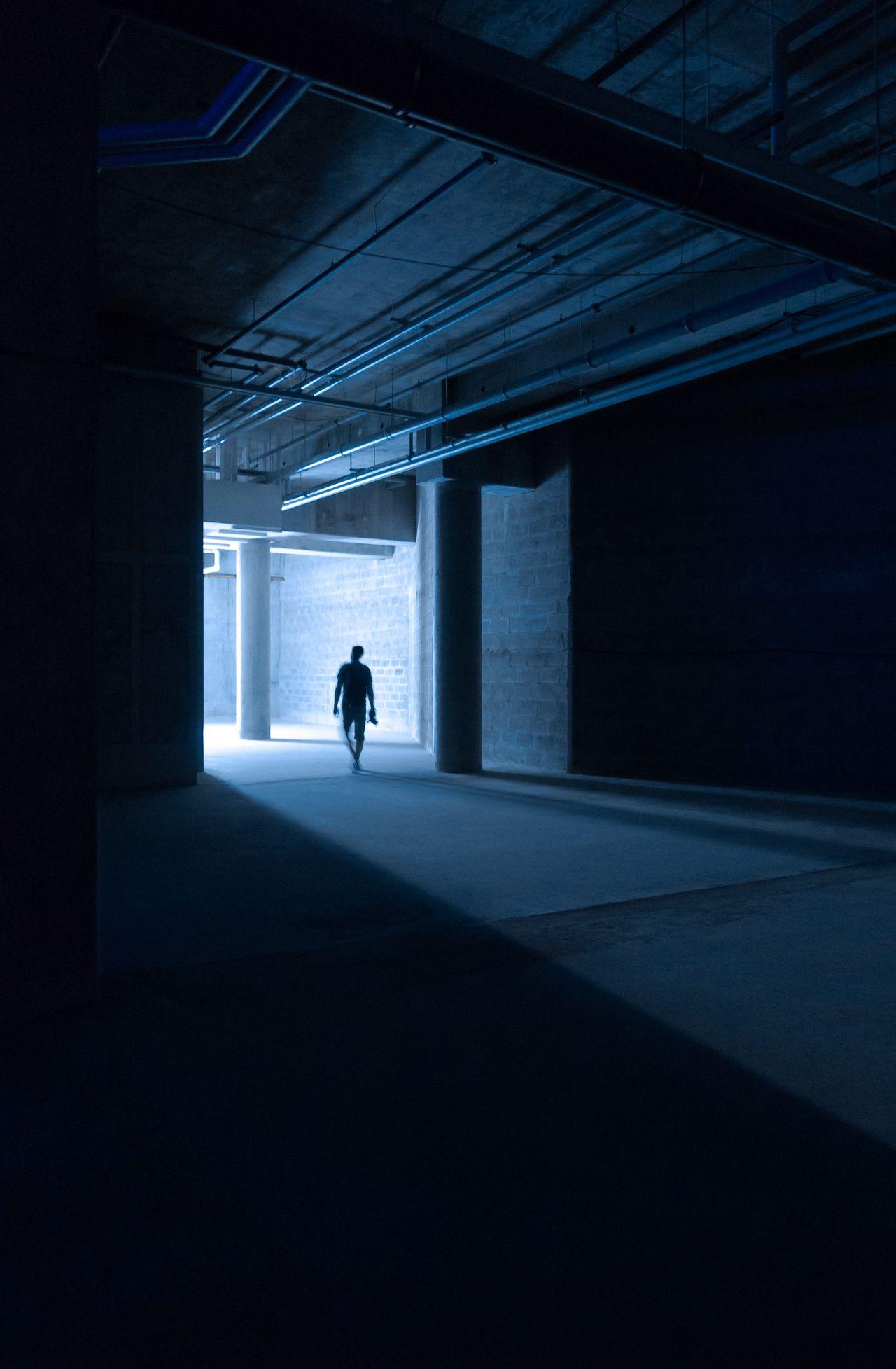 Silhouette man walking in parking garage