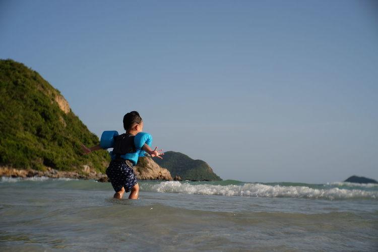 Playful Boy At Beach Against Clear Sky