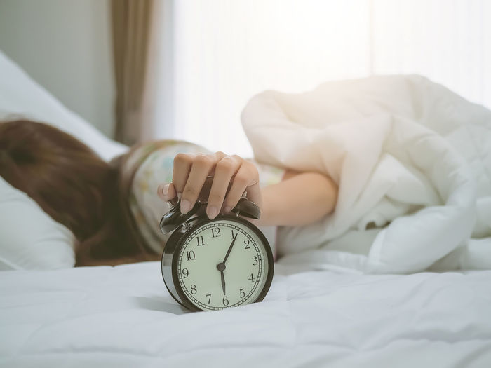 Woman lying on bed while holding alarm clock