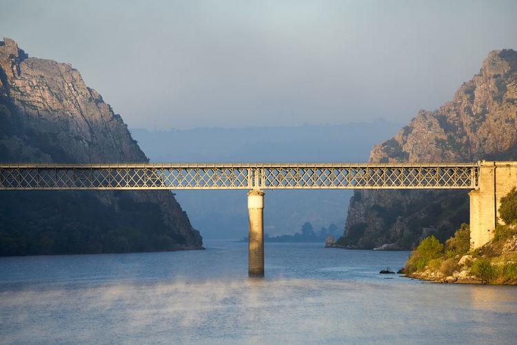 Bridge over mountain against sky