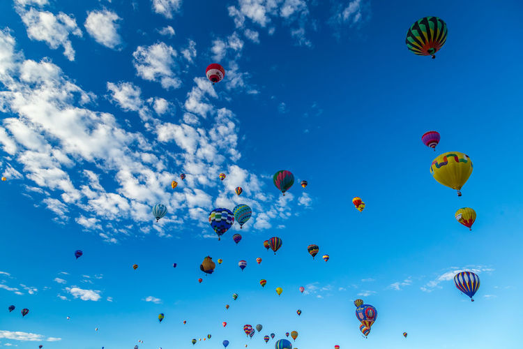 Hot Air Balloons fly over the city of Albuquerque, New Mexico during the mass ascension at the annual International Hot Air Balloon Fiesta in October, 2016 Ballooning Festival Blue Celebration Cloud - Sky Day Flying Freedom Hot Air Balloon Low Angle View Mid-air Multi Colored Nature No People Outdoors Sky Traditional Festival Variation