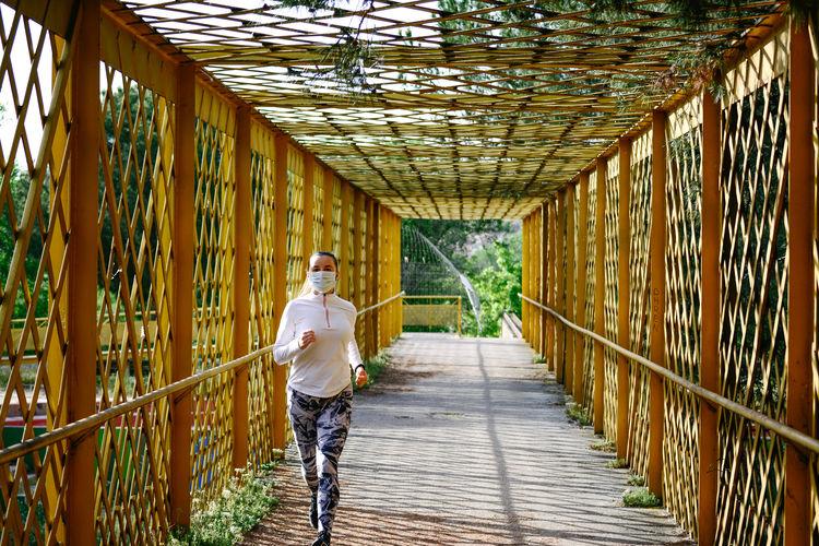 Woman wearing mask running on footbridge