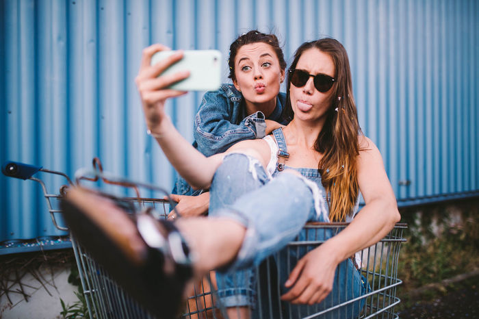 Friends making face while taking selfie through mobile phone