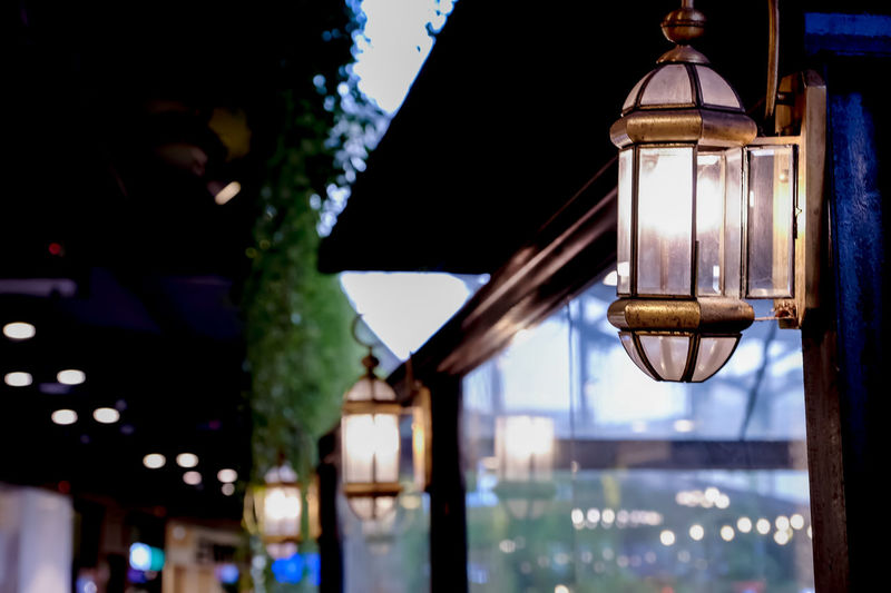 Low angle view of illuminated lamp hanging on building