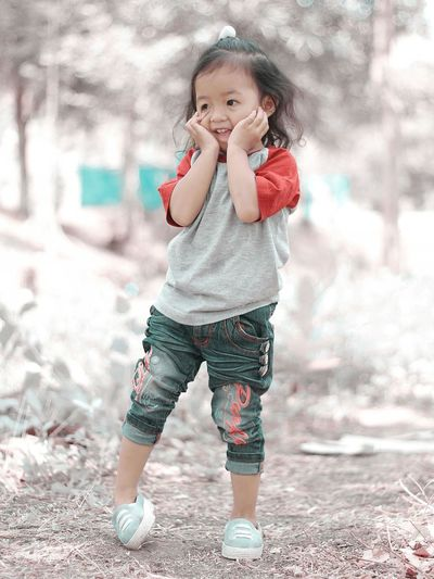 Smiling girl standing on field