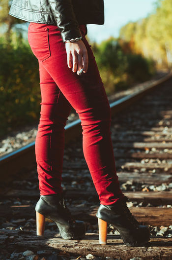 Low section of woman standing on railroad tie