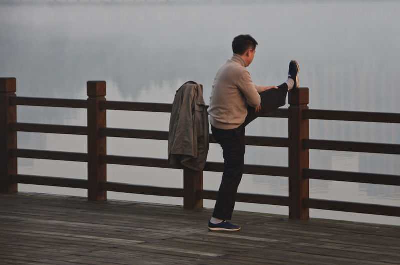 Shanghai Streets Stretching Legs Lifestyles One Person Outdoors Railing Real People Rear View Standing Street Photography Stretching Water