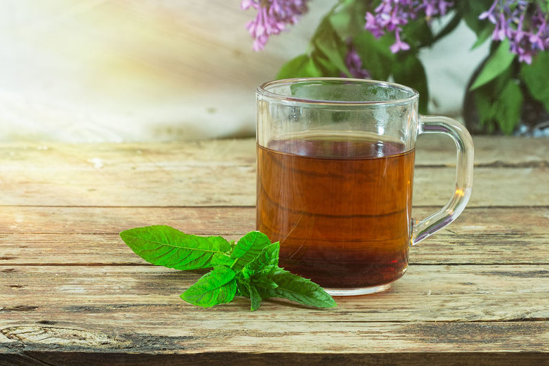Mint tea in cup on wooden table