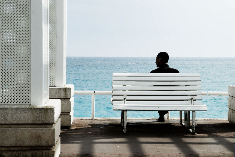 Rear view of woman sitting on bench by sea against clear sky