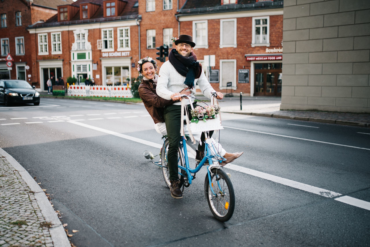 PEOPLE RIDING BICYCLES ON ROAD IN CITY