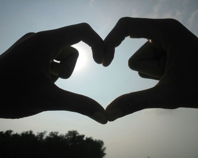 Close-up of silhouette hand against heart shape against sky