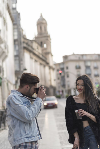 Boyfriend Photographing Girlfriend While Standing On City Street