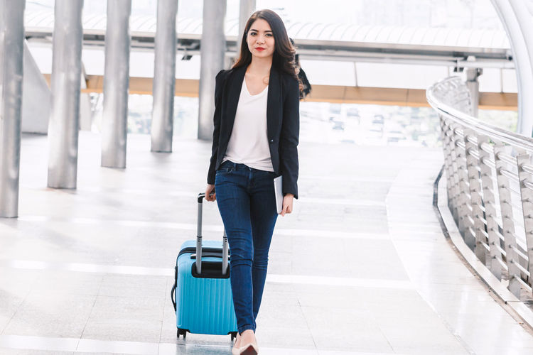Happy successful businesswoman walking with luggage One Person Full Length Young Adult Beauty Luggage Young Women Travel Beautiful Woman Front View Looking At Camera Adult Women Real People Confidence  Airport Lifestyles Walking Portrait Suitcase Fashion