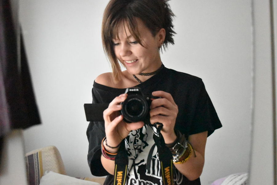 Photography Themes Camera - Photographic Equipment Holding One Woman Only Only Women One Person Adults Only Adult Old-fashioned People Smiling Cheerful Black Hair Women Photographer Senior Adult Technology Indoors  Home Video Camera Filming