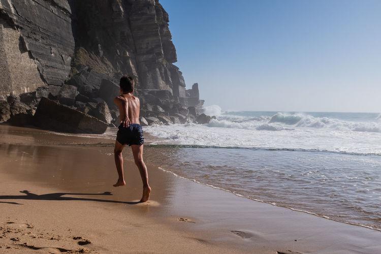 Rear view of boy in blue swim shorts running on sea shore.