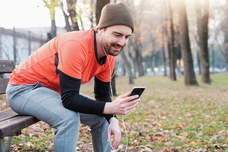 Autumn Beard Clothing Communication Connection Leisure Activity Lifestyles Men Mobile Phone One Person Outdoors Portable Information Device Real People Smart Phone Smiling Technology Tree Warm Clothing Wireless Technology Young Adult Young Men